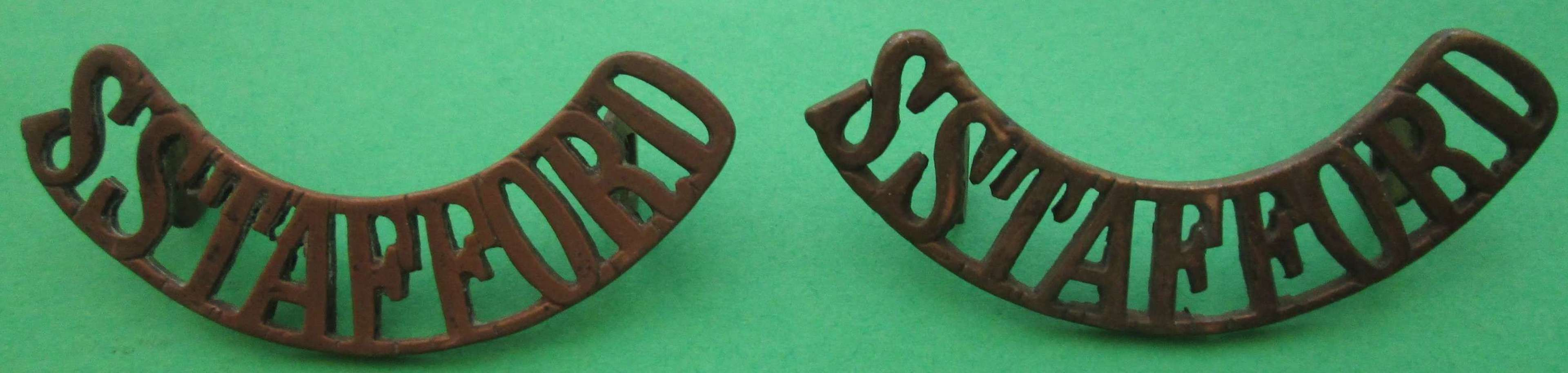 A PAIR OF STAFFORDSHIRE METAL SHOULDER TITLES