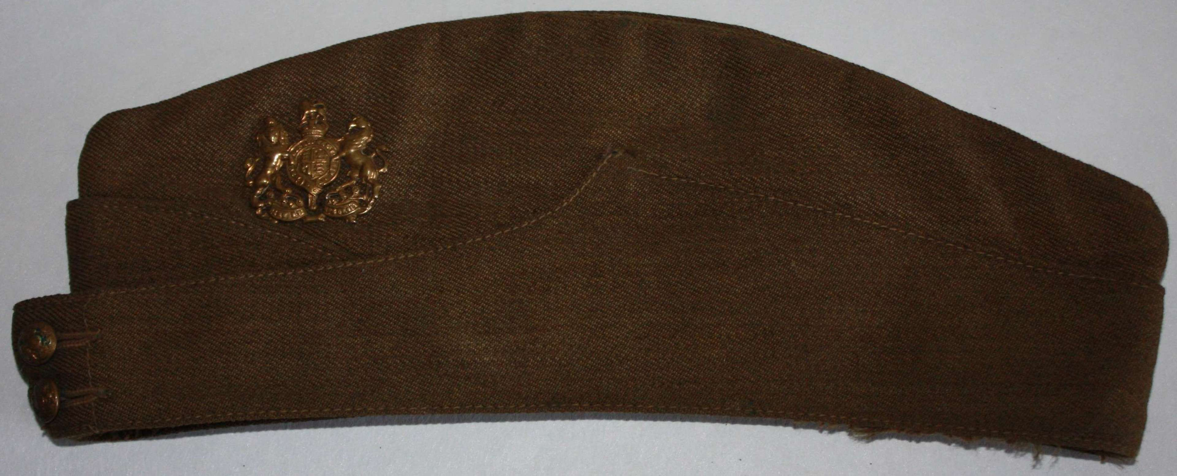 A GOOD WWII BRITISH ISSUE ARMY SIDE CAP NAMED AND BADGED